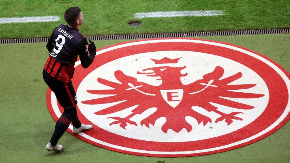 Luka Jovic streift sich das Eintracht-Trikot über. Auf dem Boden liegt ein riesiges Eintracht-Wappen.