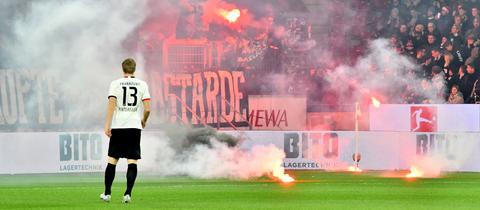 Martin Hinteregger sieht, wie aus dem Eintracht-Block Pyrotechnik auf den Rasen fliegt.