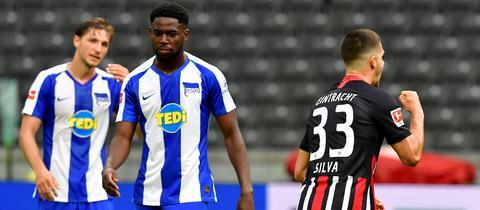 André Silva steht neben zwei Hertha-Spielern