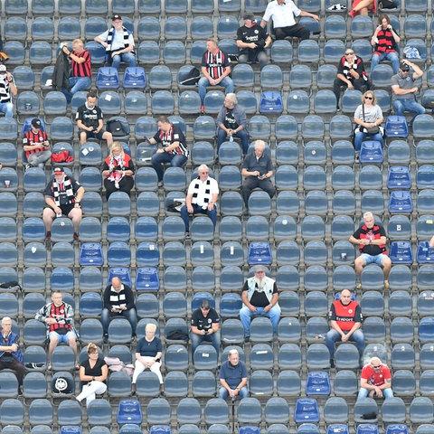 Einige Fans schauen das Spiel der Eintracht gegen Bielefeld im Frankfurter Stadion.
