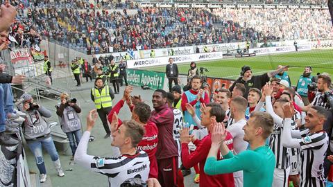 Die Spieler der Eintracht feiern den Sieg über Augsburg gemeinsam mit den Fans.