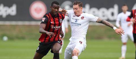 Evan N'Dicka von Eintracht Frankfurt im Zweikampf mit Manuel Schäffler vom 1. FC Nürnberg