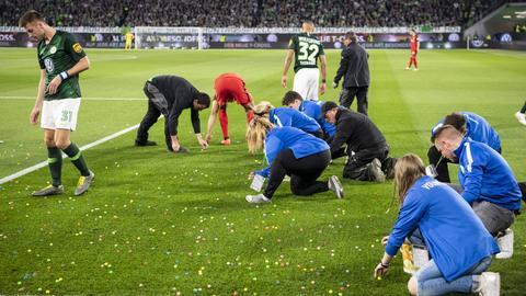 Spieler und Helfer sammeln Ostereier vom Wolfsburger Rasen.
