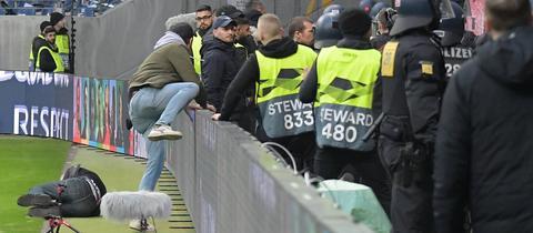 Ein Eintracht-Fan stürzt über eine Bande