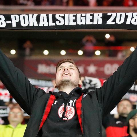 """Ein Fußball-Fan jubelt und reißt die Arme hoch. Dabei hält er einen Schal in den Händen, auf dem steht """"dfb-Pokalsieger 2018""""."""