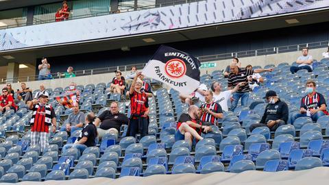 Zuschauer auf einer Tribüne im Stadion. Mittendrin eine Fahne mit dem Logo von Eintracht Frankfurt.
