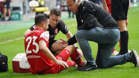 Fortuna Düsseldorfs Niko Gießelmann wird im Spiel gegen Schalke behandelt.