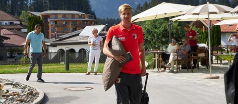 Martin Hinteregger kommt mit Kissen und Buch im Augsburger Trainingslager an.