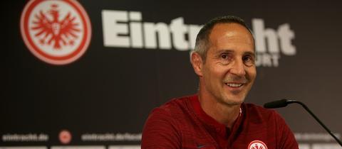 Adi Hütter lächelt im Pressereaum der Eintracht