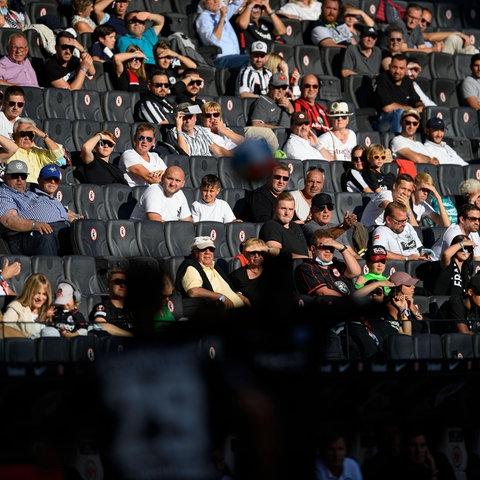 Zuschauer auf der Haupttribüne beim Eintracht-Spiel gegen Köln. Im Vordergrund ein Zweikampf auf dem Spielfeld.