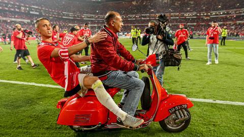 Odysseas Vlachodimos sitzt auf einem Moped hinten und wird über den Platz gefahren.