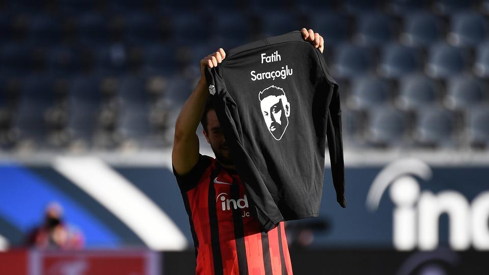 Amin Younes hält ein T-Shirt an Gedenken an die Opfer von Hanau hoch