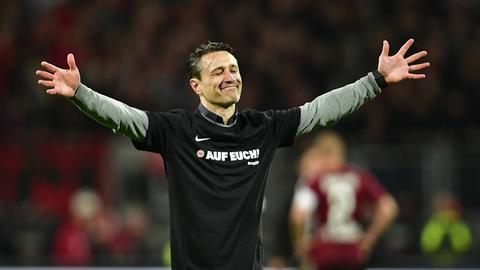 Eintracht-Trainer Niko Kovac streckt die Arme aus und schließt die Augen.