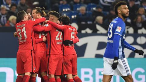 Während die Eintracht ihren Torschützen Meier feiert, schleicht Schalkes Choupo-Moting in Richtung Anstoßpunkt.