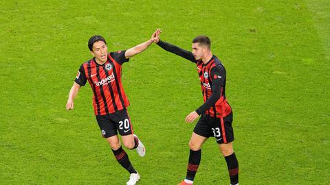 Makoto Hasebe und André Silva von Eintracht Frankfurt klatschen sich ab.