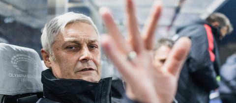 Armin Veh hält seine Hand vor eine Kamera-Linse.