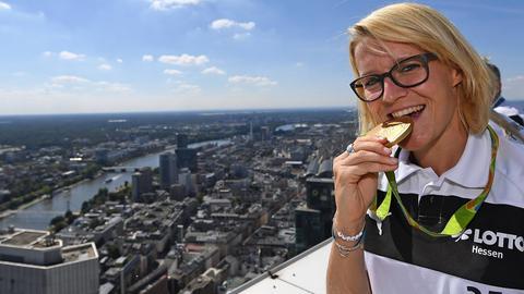Saskia Bartusiak beißt auf einem Frankfurter Hochhaus in ihre Gold-Medaille.