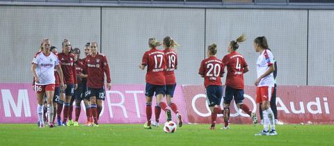 Die Spielerinnen des FC Bayern jubeln, einige Frankfurterinnen schauen bedrückt drein.