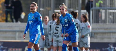 Zwei FFC-Spielerinnen schauen enttäuscht, im Hintergrund bejubelt Bayer Leverkusen das 1:0