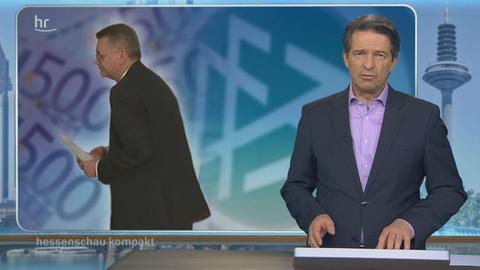 Das hessenschau-Studio mit dem Moderator im Vordergrund und einem Bild von Reinhard Grindel im Hintergrund.