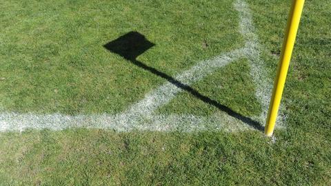Eckfahne wirft Schatten auf Fußballfeld