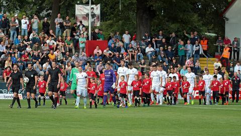 Der FC Gießen und Steinbach Haiger laufen auf den Platz.