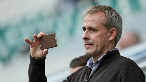 Littbarski macht mit seinem Handy ein Foto.