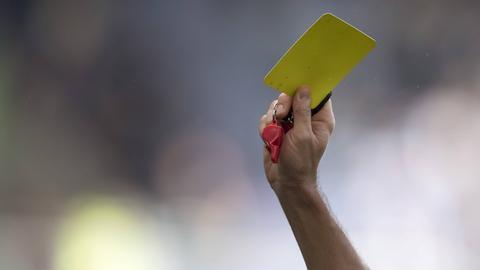 Symbolbild mit Schiedsrichter und Pfeife und Gelbe Karte