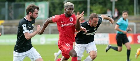 Dennis Owusu vom FC Gießen setzt sich gegen zwei Gegenspieler durch.