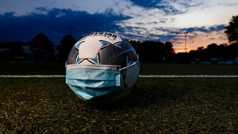 Ein Fußball mit Mundschutz liegt in der Abenddämmerung auf einem Spielfeld.