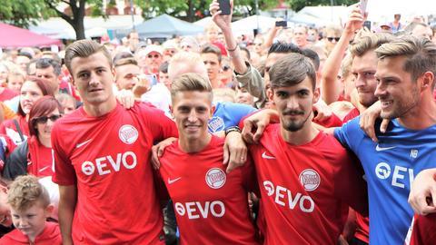 Kickers-Spieler posieren mit Fans