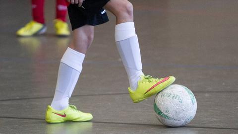 Die Beine eines Hallenfußballers mit Ball