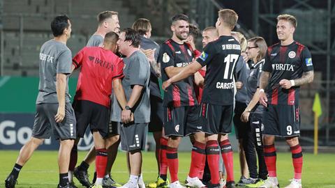 Die Mannschaft des SV Wehen Wiesbaden klatscht sich zufrieden auf dem Platz ab.