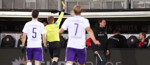 Schiedsrichter Patrick Ittrich zeigt Rüdiger Rehm die Gelbe Karte.