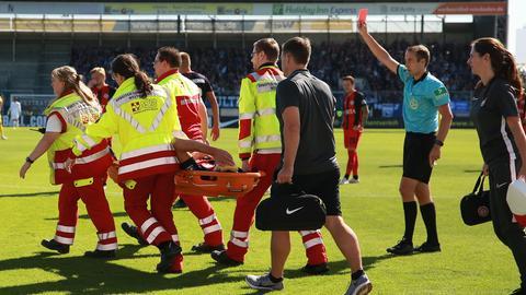 Benedikt Röcker wird beim Spiel gegen Bielefeld verletzt vom Platz getragen - und sieht Rot für sein Foul.