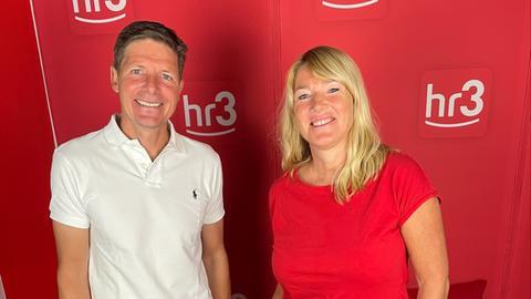 Der neue Eintracht-Coach Oliver Glasner und hr3-Moderatorin Tanja Rösner stehen vor einer roten Wand, auf der hr3-Logos wie ein regelmäßiges Muster angeordnet sind.