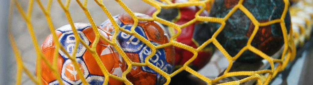 Handbälle liegen in einem Tornetz