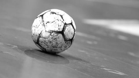 Ein Handball liegt auf einem Spielfeld.