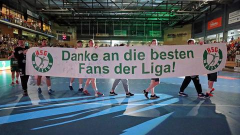 """Spieler der HSG Wetzlar halten ein Banner hoch: """"Danke an die besten Fans der Liga"""""""