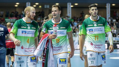 Drei Wetzlarer Spieler laufen grinsend über das Feld.