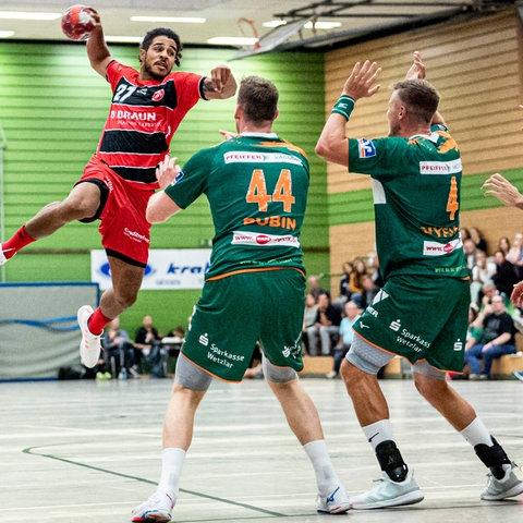 """Drei Handballer auf dem Spielfeld. Zwei versuchen einen """"Angriff"""" abzuwehren."""
