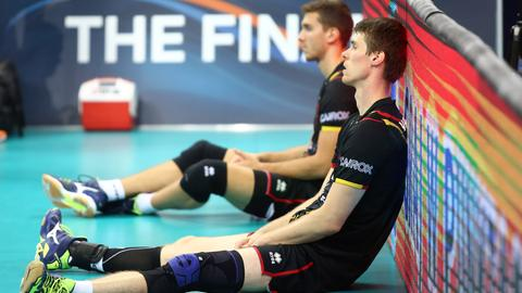 Zwei Volleyballer lehnen sich an der Bande an