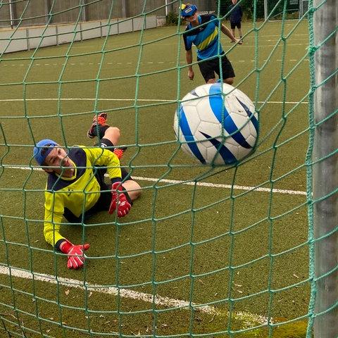 Ein Ball fliegt ins Tor (von einer Position hinter dem Tor fotogafiert). Der Tormann liegt nach seinem Abwehrversuch auf dem Boden und schaut ihm nach. Dahinter der Fußballer, der den Bal geschossen hat.
