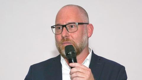 Mercenaries-Präsident Carsten Dalkowski bei einer Rede mit Mikrofon