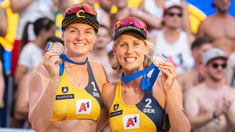 Die Drittplatzierten Karla Borger (r.) und Julia Sude zeigen ihre Medaillen bei der Siegerehrung.