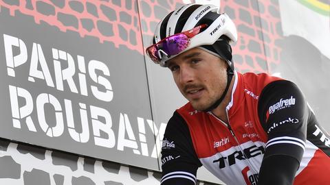 """John Degenkolb vor einem Schild, auf dem """"Paris Roubaix"""" steht."""