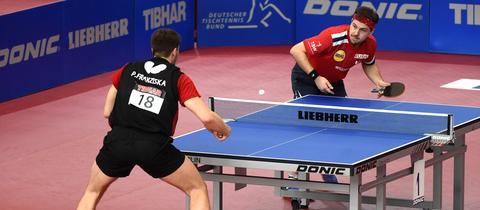 Timo Boll und Patrick Franziska stehen sich an der Tischtennis-Platte gegenüber.