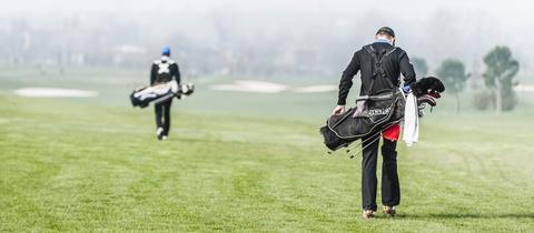 Zwei Männer, die ihre Golftaschen über den Platz tragen, von hinten.