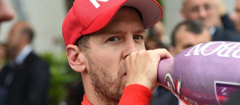 Sebastian Vettel trinkt aus einer Sektflasche