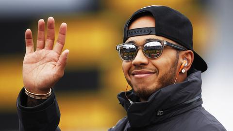 Hamilton grinst und winkt.